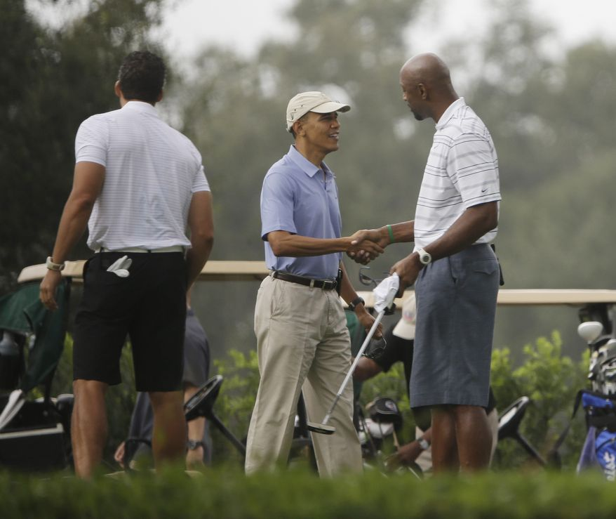 President Barack Obama, center, shakes hands with former NBA basketball player Alonzo Mourning, right, at Grande Oaks golf club, Saturday, Nov. 9, 2013 in Ft. Lauderdale, Fla. Obama traveled to the Miami area yesterday for a series of private Democratic fundraisers and a golf outing today.  (AP Photo/Pablo Martinez Monsivais)