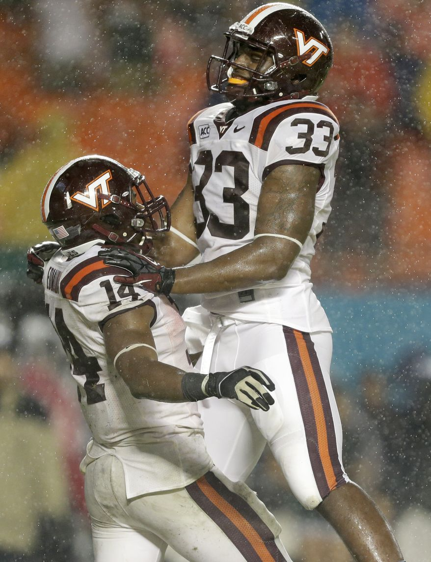 Virginia Tech running back Trey Edmunds (14) celebrates with tight end Darius Redman (33) after Edmunds scored a touchdown during the second half of an NCAA college football game against Miami, Saturday, Nov. 9, 2013, in Miami Gardens, Fla. Edmunds ran for four touchdowns, the first three of them set up by Miami special-teams miscues, and Virginia Tech knocked off the 14th-ranked Hurricanes 42-24. (AP Photo/Wilfredo Lee)