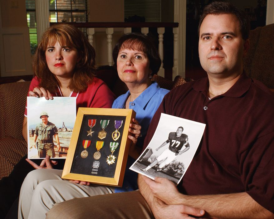 Jill Kalsu-Horning, left, and Bob Kalsu Jr., right, pose with their mother, Jan Kalsu McLauchlin, and pictures of Bob Kalsu Sr. and his medals Friday, April 30, 2004 in Edmond, Okla. Kalsu Sr., an All-American lineman at the University of Oklahoma and a Buffalo Bills player, was one of three NFL players to serve in Vietnam, and the only to die in that conflict. (AP Photo/Jeffrey Haderthauer)
