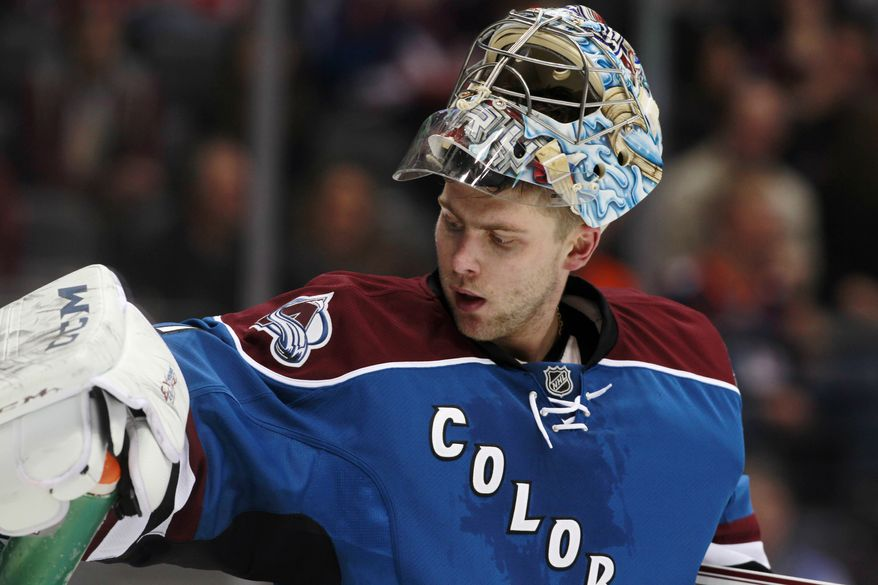 Colorado Avalanche goalie Semyon Varlamov, of Russia, reaches for his water bottle on top of the net during a timeout against the Washington Capitals in the second period of an NHL hockey game in Denver on Sunday, Nov. 10, 2013. (AP Photo/David Zalubowski)