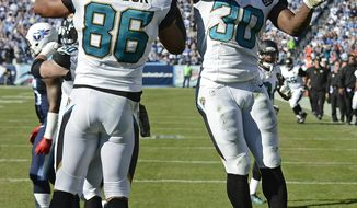 Jacksonville Jaguars running back Jordan Todman (30) celebrates with Clay Harbor (86) after Todman scored a touchdown on a 5-yard run against the Tennessee Titans in the third quarter of an NFL football game on Sunday, Nov. 10, 2013, in Nashville, Tenn. (AP Photo/Mark Zaleski)