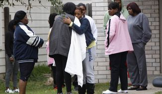 Family and friends console one another outside a home in Cypress, Texas, on Sunday, Nov. 10, 2013, after two people were killed and at least 22 others were injured Saturday night when gunfire rang out at a large birthday party in the Houston suburb, sending partygoers fleeing in panic, authorities said. Authorities say they're seeking two gunmen. (AP Photo/Bob Levey)