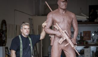 Sculptor Gregory Marra stands next to the memorial statue in tribute of Chris Kyle.