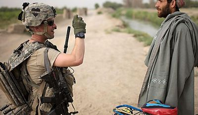 U.S. Army 1st Lt. Christopher Babcock, from New Orleans, La., photographs an Afghan villager for intelligence purposes after he was stopped cycling near COP Nolen, in the volatile Arghandab Valley, Kandahar, Afghanistan, Thursday, July 22, 2010. (AP Photo/Rodrigo Abd)