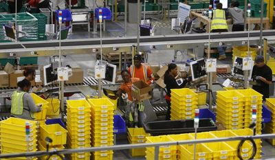 Amazon employees process orders at the company's San Bernardino Fulfillment Center on Tuesday, Oct. 29, 2013, in San Bernardino, Calif. (AP Photo/David McNew)