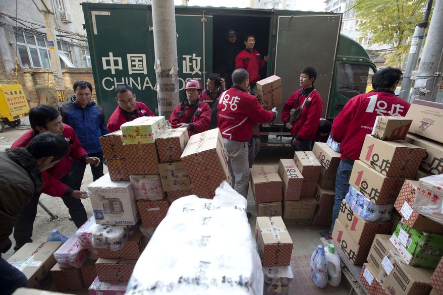 """Deliverymen for an online shopping portal sort through goods at a distribution center in Beijing on Monday, Nov. 11, 2013. The date, dubbed """"Singles' Day"""" because unattached young people go on a gift-giving binge to woo each other, has evolved into China's, and possibly the world's, busiest online shopping day. (AP Photo/Ng Han Guan)"""