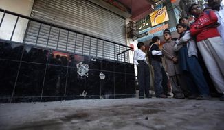 Pakistani youths gather at the spot at which Nasiruddin Haqqani, a senior leader of the feared militant Haqqani network, was assassinated at an Afghan bakery in the Bhara Kahu area on the outskirts of Islamabad on Monday, Nov. 11, 2013. (AP Photo/Anjum Naveed)