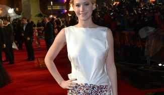 """** FILE ** American actress Jennifer Lawrence poses for photographers as she arrives on the red carpet for the World Premiere of """"The Hunger Games: Catching Fire,"""" on Monday Nov. 11,  2013, in Leicester Square, London. (Photo by Jon Furniss/Invision/AP)"""