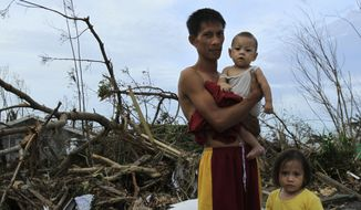 Roy Cagbian, 28, stands with his daughters, 7-month-old Shandev and 3-year-old Ashley in front of their home destroyed by Typhoon Haiyan in Tacloban, central Philippines, Monday, Nov. 11, 2013. Typhoon Haiyan, one of the strongest storms on record, slammed into six central Philippine islands on Friday leaving a wide swath of destruction and hundreds of people dead. (AP Photo/Wally Santana)