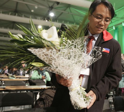 Naderev Sano from the Philippine  holds flowers that where  presented by other nations and organizations as a sympathy symbol for the Philippine people hit by Typhoon Haiyan during the United Nations Climate Change Conference in Warsaw, Poland, Monday, Nov. 11, 2013. (AP Photo/Czarek Sokolowski)