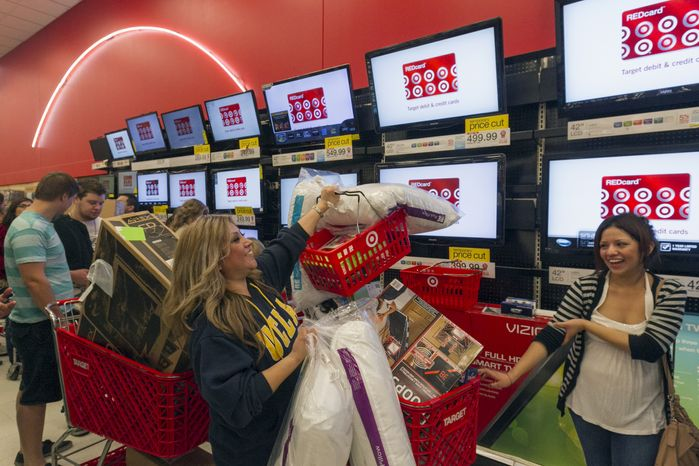 ** FILE ** Shopper Roxanna Garcia (middle) waits in line to pay for more than $1,000 in gifts at the Target store in Burbank, Calif., on Thursday, Nov. 22, 2012. (AP Photo/Damian Dovarganes)