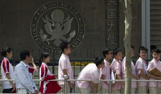 Chinese students wait outside the U.S. Embassy in Beijing on Wednesday, May 2, 2012, for their visa application interviews. (AP Photo/Alexander F. Yuan)