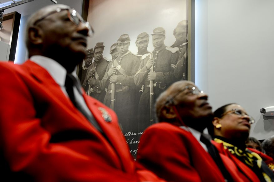 Members of the east coast chapter of the Tuskegee Airmen  sit in front of large photographs of African American Civil War solders during a Veterans Day Wreath Laying and Commemoration at the African American Civil War Memorial Museum on Veterans Day, Washington, D.C., Monday, November 11, 2013. (Andrew Harnik/The Washington Times)