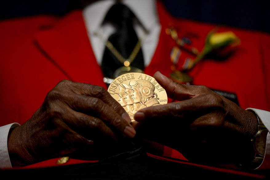 Tuskegee Airman Major Louis Anderson Jr. holds up his Congressional Medal of Honor, presented to him by  Rep. Eleanor Holmes-Norton (D-D.C.) during a Veterans Day Wreath Laying and Commemoration at the African American Civil War Museum on Veterans Day, Washington, D.C., Monday, November 11, 2013. (Andrew Harnik/The Washington Times)