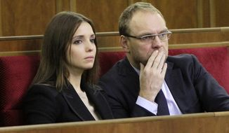 Eugenia Tymoshenko (left), daughter of imprisoned former Ukrainian Prime Minister Yulia Tymoshenko, and Serhiy Vlasenko, the lawyer for the jailed politician, watch a parliament session in Kiev on Friday, Nov. 8, 2013. Opposition leader Arseniy Yatsenyuk told a parliamentary committee hearing on Monday he had received a text message from Mr. Vlasenko saying that he had been arrested. (AP Photo/Sergei Chuzavkov)