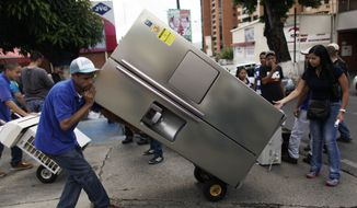 "A man transports a recently purchased refrigerator on a dolly, outside an appliance store in Caracas, Venezuela, Monday, Nov. 11, 2013. President Nicolas Maduro seized control of a nationwide chain of appliance stores Friday seeking to battle inflation and shortages. Shoppers were still arriving Monday to join the hundreds who began amassing over the weekend after price inspectors said they found evidence of ""usury"" and Maduro ordered the chain Tiendas Daka ""occupation."" (AP Photo/Ariana Cubillos)"