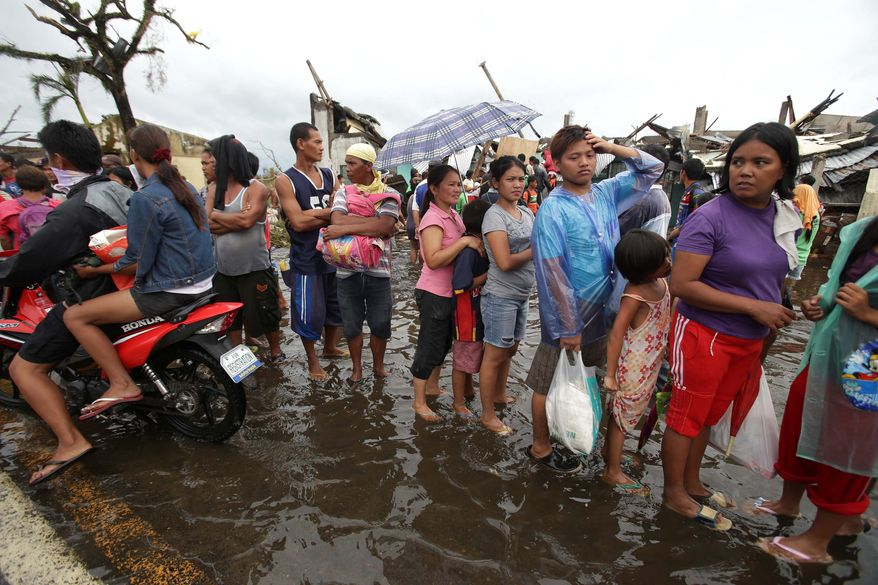 Survivors wait in line for relief goods on a flooded road at typhoon-ravaged Tacloban in central Philippines on Tuesday. (Associated Press)
