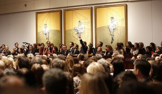 "This Tuesday, Nov. 12, 2013 photo provided by Christie's New York shows the bidding during the auction for the 1969 painting by Francis Bacon, ""Three Studies of Lucian Freud"" in New York. ""Three Studies of Lucian Freud"" was sold at Christie's postwar and contemporary art sale for over $142 million in New York, a record for most expensive artwork ever sold at auction. (AP Photo/Christie's Images LTD. 2013)"