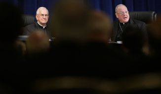 Archbishop Joseph Kurtz, left, of Louisville, Kentucky, vice president of the United States Conference of Catholic Bishops, and Cardinal Timothy Dolan, right, of New York, conference president, are seen past fellow bishops during the conference's annual fall meeting in Baltimore, Tuesday, Nov. 12, 2013. Kurtz was elected to a three-year term for president of the conference after serving the last three years as vice-president under the outgoing Dolan. (AP Photo/Patrick Semansky)