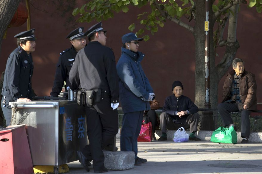 Elderly Chinese women sit on the sidewalk near a checkpoint set up as part of increased security during a weekend gathering of the Communist Party's 205-member Central Committee for its third annual plenum in Beijing on Tuesday, Nov. 12, 2013. In a brief statement China's leaders promised to give the free market an even bigger role as they overhaul the worn-out growth model of their slowing, government-dominated economy. (AP Photo/Ng Han Guan)