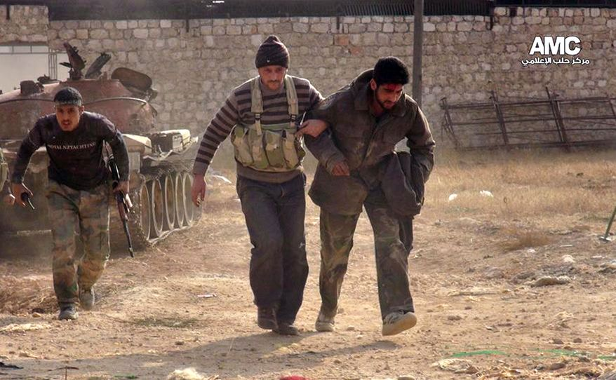 This Monday, Nov. 11, 2013, citizen journalism image provided by Aleppo Media Center AMC, which has been authenticated based on its contents and other AP reporting, shows two Free Syrian Army fighters helping a wounded comrade during clashes in Aleppo, Syria. (AP Photo/Aleppo Media Center AMC)