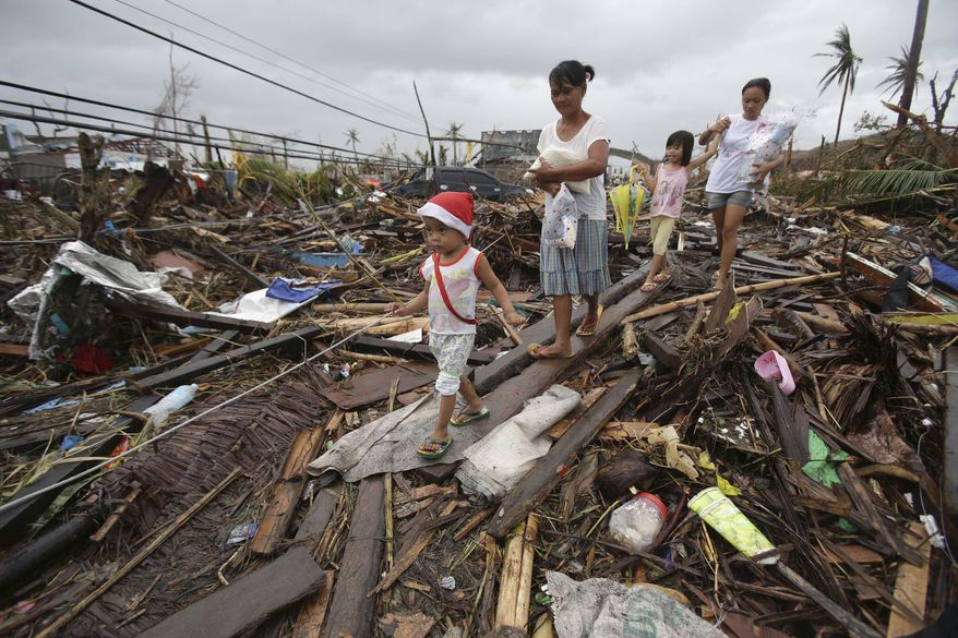 Survivors walk in typhoon ravaged Tacloban city, Leyte province, central Philippines on Tuesday, Nov. 12, 2013. The Philippines emerged as a rising economic star in Asia but the trail of death and destruction left by Typhoon Haiyan has highlighted a key weakness: fragile infrastructure resulting from decades of neglect and corruption. (AP Photo/Aaron Favila)