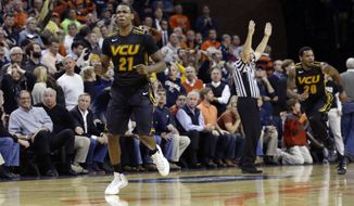 Virginia Commonwealth guard Treveon Graham (21) reacts to his winning three-point shot during the second half of an NCAA college basketball game in  Charlottesville, Va., Tuesday, Nov. 12, 2013.  VCU won 59-56.  (AP Photo/Steve Helber)