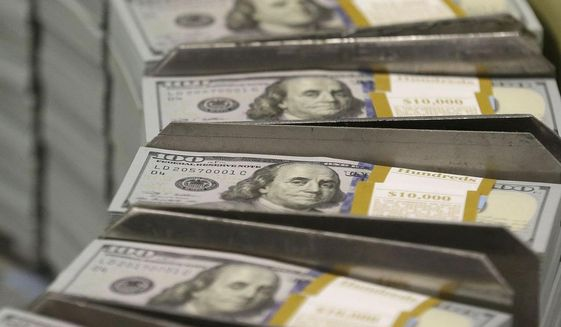Just-cut stacks of $100 bills make their way down the production line at the Bureau of Engraving and Printing's Western Currency Facility in Fort Worth, Texas, on Tuesday, Sept. 24, 2013. (AP Photo/LM Otero)