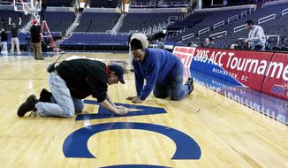 Kim Webster, left, and Phil Westmoreland place the ACC logo on the floor of the MCI Center in Washington, Wednesday, March 9, 2005 prior to the start Thursday of the Atlantic Coast Conference basketball tournament. (AP Photo/Lawrence Jackson)