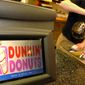A Dunkin' Donuts employee pours coffee for a customer in Cambridge, Mass., on Dec. 8, 2005. (Associated Press) **FILE**