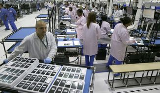 Workers man the Motorola smartphone plant in Fort Worth, Texas, on Tuesday, Sept. 10, 2013. (AP Photo/LM Otero)