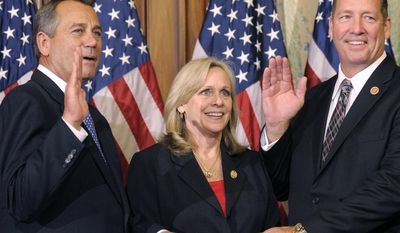FILE - In this Jan. 3, 2013 file photo, House Speaker John Boehner of Ohio, left, performs a mock swearing in for Rep. Ted Yoho, R-Fla., right, accompanied by his wife Carolyn, on Capitol Hill in Washington as the 113th Congress began. As a Republican, freshman Yoho cares about the Republican Party's image and fate. But what he especially cares about is a tiny sliver of the GOP: about 22,000 primary voters who lean heavily conservative, and who secured his spot in the House of Representatives. Yoho is hardly alone. Many other House Republicans owe their elections to similarly small and ideologically intense electorates. These GOP lawmakers pay far less attention to the party's national reputation. And that deeply frustrates activists trying to build broad, national coalitions to elect a Republican as president in 2016 and beyond. (AP Photo/Cliff Owen, File)
