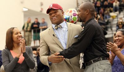 Woodbridge High School football player Da'Shawn Hand, center, celebrates with his mother Nicole Graham, left, and father Sharif Hand after announcing his decision to attend the University of Alabama Thursday, Nov. 14, 2013, at Woodbridge High School in Woodbridge, Va. (AP Photo/The Potomac News, Marcus J. Wilson)