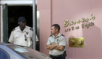 Security guards stand in front of the now-closed Brennan's Restaurant in New Orleans on Friday, June 28, 2013. (AP Photo/Gerald Herbert)