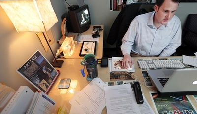 Jeremy Bills works at his job as associate director at the Nashville Education Community and Arts Television office on Wednesday, Nov. 13, 2013, in Nashville, Tenn. Bills, originally from Tampa, Fla., received his master's degree from Vanderbilt University in Nashville and has stayed in his college town while trying unsuccessfully to find a job in his field of study. (AP Photo/Mark Humphrey)
