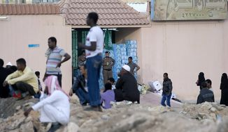 In this Wednesday, Nov. 13, 2013 photo, Saudi security forces watch Ethiopians gather as they wait to be repatriated in Manfouha, southern Riyadh, Saudi Arabia. In Saudi Arabia, garbage has piled up on streets around the mosque housing the tomb of the Prophet Muhammad. Groceries stores have shut their doors and almost half of the kingdom's small construction firms have stopped working on projects. The economic chaos comes as part of Saudi Arabia's crackdown on migrant workers, which began Nov. 4, targets the country's more than 9 million foreign laborers. Decades of lax immigration enforcement allowed migrants to take low-wage manual, clerical and service jobs that the kingdom's own citizens shunned for better paying, more comfortable work. (AP Photo)