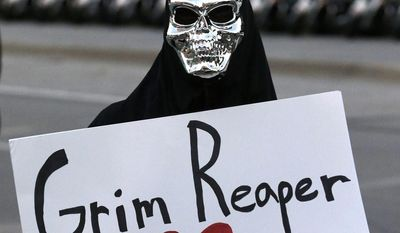 ** FILE ** An unidentified protestor wears a costume and holds a sign across the street where President Barack Obama was visiting the Temple Emanu-El in Dallas, Wednesday, Nov. 6, 2013. (AP Photo/LM Otero)