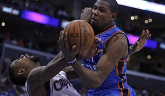 Oklahoma City Thunder forward Kevin Durant, right, collides with Los Angeles Clippers center DeAndre Jordan, left, going to the basket in the second half of their NBA basketball game Wednesday, Nov. 13, 2013, in Los Angeles. The Clippers won the game 111-103.  (AP Photo/Alex Gallardo)