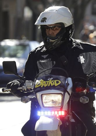 """A San Francisco Police Officer with a Batkid sign on his bike waits for the arrival of Miles Scott, dressed as Batkid, in San Francisco, Friday, Nov. 15, 2013. San Francisco turned into Gotham City on Friday, as city officials helped fulfill Scott's wish to be """"Batkid.""""Scott, a leukemia patient from Tulelake in far Northern California, was called into service on Friday morning by San Francisco Police Chief Greg Suhr to help fight crime, The Greater Bay Area Make-A-Wish Foundation says. (AP Photo/Jeff Chiu)"""