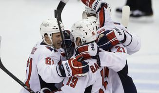 Washington Capitals center Nicklas Backstrom (19) is congratulated by teammates after his shootout goal on Detroit Red Wings goalie Jimmy Howard in an NHL hockey game in Detroit, Friday, Nov. 15, 2013. The Capitals won 4-3.(AP Photo/Carlos Osorio)