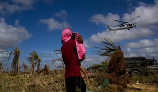A Typhoon Haiyan survivor carries a child wrapped in a towel as he watches a helicopter landing to bring aid to the destroyed town of Guiuan, Samar Island, Philippines, Friday, Nov. 15, 2013. As an international aid effort gathered steam, resilient Filipinos in battered towns started rebuilding their lives and those of their neighbors - with or without help from their government or foreign aid groups. (AP Photo/David Guttenfelder)