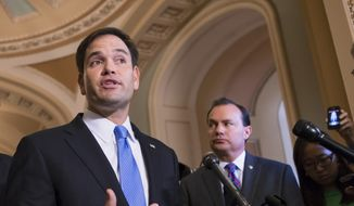 Sen. Marco Rubio (left), Florida Republican, accompanied by Sen. Mike Lee, Utah Republican, speaks to reporters during a news conference on Capitol Hill in Washington in this Sept. 27, 2013, file photo. (AP Photo/J. Scott Applewhite, File) ** FILE **