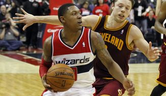 Washington Wizards guard Bradley Beal, left, gets past Cleveland Cavaliers guard Matthew Dellavedova in overtime of an NBA basketball game on Saturday, Nov. 16, 2013, in Washington. The Cavaliers won 103-96 in overtime. (AP Photo/Alex Brandon)