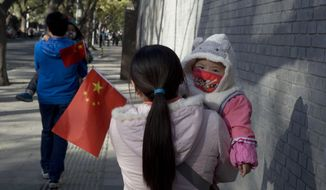 Visitors to the forbidden city carry children holding the Chinese national flags in Beijing, China, Saturday, Nov. 16, 2013. Some 15 million to 20 million Chinese parents will be allowed to have a second baby after the Chinese government announced Friday, Nov. 15, 2013, that couples where one partner has no siblings can have two children, in the first significant easing of the country's strict one-child policy in nearly three decades. (AP Photo/Ng Han Guan)