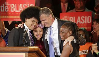 FILE - In this Tuesday, Sept. 10, 2013 file photo, New York Democratic mayoral candidate Bill de Blasio embraces his son Dante, left, daughter Chiara, second left, and wife Chirlane McCray after polls closed in the city's primary election in New York. De Blasio and his wife settled in the Park Slope neighborhood of the Brooklyn borough of New York largely because they felt that their interracial relationship would be accepted there, the mayor-elect has said. (AP Photo/Kathy Willens, File)