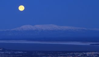 A full moon sets over Mount Susitna in Anchorage, Alaska, Nov. 17, 2013. (AP Photo/Dan Joling)