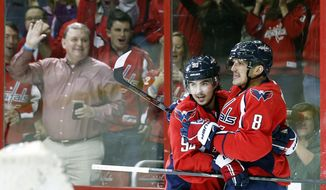 Washington Capitals center Marcus Johansson (90), of Sweden, and right wing Alex Ovechkin (8), of Russia, celebrate Ovechkin's first goal in the first period of an NHL hockey game against the St. Louis Blues, Sunday, Nov. 17, 2013, in Washington. (AP Photo/Alex Brandon)