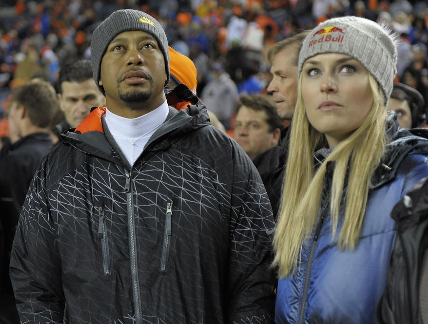 Tiger Woods, left, and Lindsey Vonn watch from the sidelines as the Denver Broncos and the Kansas City Chiefs warm up before an NFL football game, Sunday, Nov. 17, 2013, in Denver. (AP Photo/Jack Dempsey)