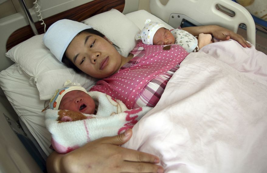In this Saturday Nov. 16, 2013 photo, a woman holds her newborn twins in a hospital in Changsha in south China's Hunan province. Experts estimate that the first easing of the country's strict one-child policy in three decades announced Friday allowing couples where one partner is an only child to have a second baby will result in 1 million to 2 million extra births per year in the first few years, on top of the 16 million babies born annually in China. (AP Photo) CHINA OUT