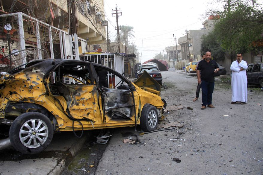 ** FILE ** On Saturday, Oct. 19, 2013, civilians inspect the aftermath of a Friday-night car bomb attack in Baghdad's eastern Mashtal neighborhood. (AP Photo/Hadi Mizban)